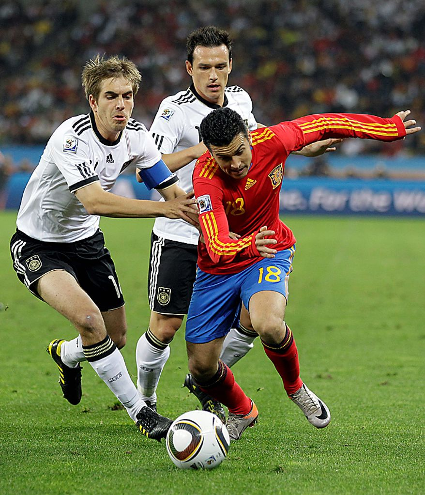 Spain's Pedro Rodriguez, right, controls the ball from Germany's Philipp Lahm, left, and Germany's Piotr Trochowski during the World Cup semifinal soccer match between  Germany and Spain at the stadium in Durban, South Africa, Wednesday, July 7, 2010.  (AP Photo/Luca Bruno)