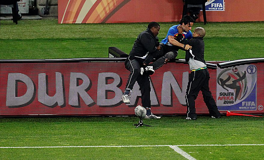 An unidentified man, center, is detained by security after invading the pitch during the World Cup semifinal soccer match between  Germany and Spain at the Moses Mabhida stadium in Durban, South Africa, Wednesday July 7, 2010. (AP Photo/Themba Hadebe)