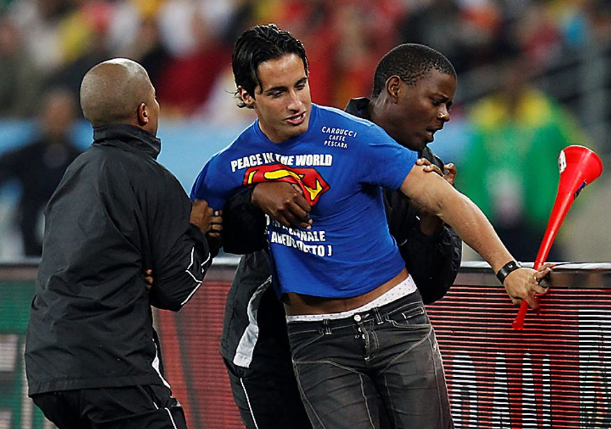 An unidentified man, center, is detained by security after invading the pitch during the World Cup semifinal soccer match between  Germany and Spain at the stadium in Durban, South Africa, Wednesday, July 7, 2010.  (AP Photo/Luca Bruno)