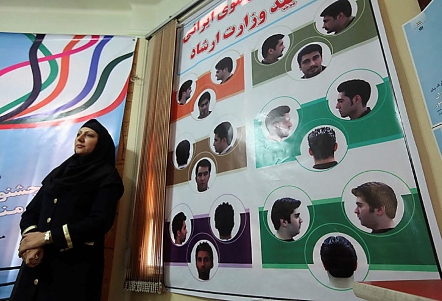 In this picture released by the semi-official Iranian Mehr News Agency, an Iranian woman stands next to a board of pictures of haircuts for men culturally appropriated by the Iran's Ministry of Culture and Islamic Guidance, in Tehran, Iran, on Monday, July 5, 2010. An Iranian fashion organization has issued a new list of culturally appropriate haircuts for men, possibly indicating a new crackdown on male attire after years of strict rules for women, Iranian media reported. (AP Photo/Mehr News Agency, Mohsen Rezaei/HO)