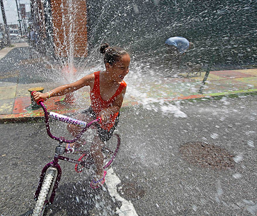 A person cools off in spraying water from a fire hydrant in the Kensington neighborhood of Philadelphia, Tuesday, July 6, 2010. The East Coast broiled under an unforgiving sun Tuesday as the temperature soared above 100 degrees in several cities. (AP Photo/Matt Rourke)