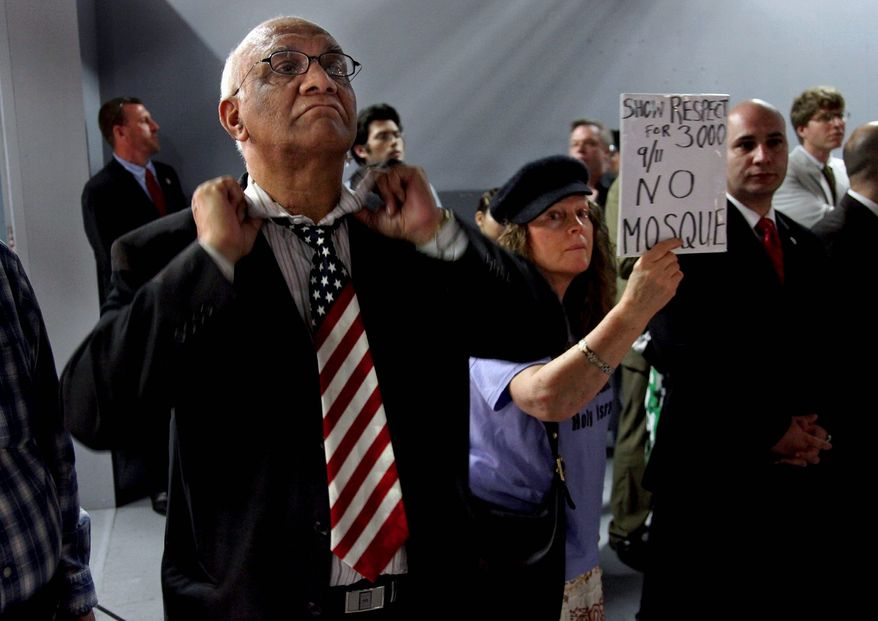 Arish Sahani puts on an American-flag tie as Linda Rivera stands in opposition to the ground zero-area mosque at a community board meeting in New York on Tuesday. Community members both for and against the plan spoke during the meeting. (Associated Press)