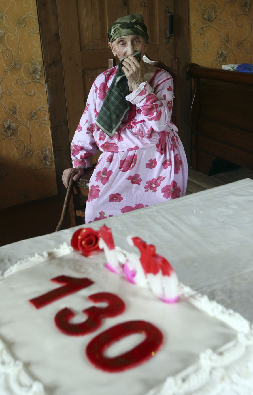 Antisa Khvichava, reportedly 130-year-old Georgian woman, looks at her birthday cake during a ceremony marking her birthday at home in the remote mountain village of Sachino 370 km (229 miles) from Georgia's capital, Tbilisi, on Thursday, July 8, 2010. Authorities in the former Soviet republic of Georgia claim Antisa Khvichava is turning 130, making her the oldest person on Earth. (AP Photo/George Abdaladze)