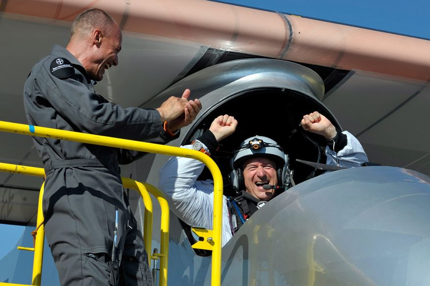 Solar Impulse's team chief Bertrand Piccard, left and Solar Impulse's Chief Executive Officer and pilot Andre Borschberg, celebrate after successfully landing the solar-powered HB-SIA prototype airplane after its first successful night flight attempt at Payerne airport on Thursday, July 8, 2010. (AP Photo/Keystone, Dominic Favre, Pool)