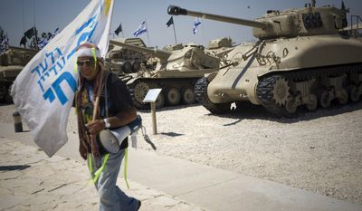 "An Israeli man walks past tanks on display in the Armored Corps Memorial and Museum near Jerusalem during a rally in support of a captured Israeli soldier Gilad Schalit on Wednesday, July 7, 2010. Text on flag reads in Hebrew: ""Gilad is still alive."" (AP Photo/Ariel Schalit)"