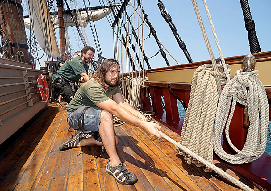 "Zack Lash, right, and Rich O'Connor haul on a halyard  on the HMS Bounty on Lake Erie off Cleveland, Wednesday, July 7, 2010. The sailing ship, built for the 1961 movie ""Mutiny on the Bounty,"" is one of 11 tall ships that will be in the city for a weekend festival. (AP Photo/Mark Duncan)"