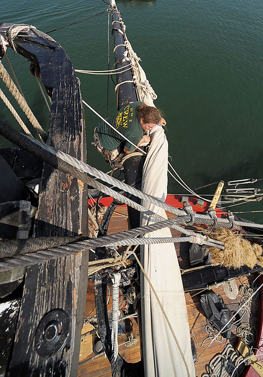 "Jesse Ludke loosens a sail on the HMS Bounty before departing Cleveland for Lake Erie, Wednesday, July 7, 2010. The sailing ship, built for the 1961 movie ""Mutiny on the Bounty,"" is one of 11 tall ships that will be in the city for a weekend festival. (AP Photo/Mark Duncan)"