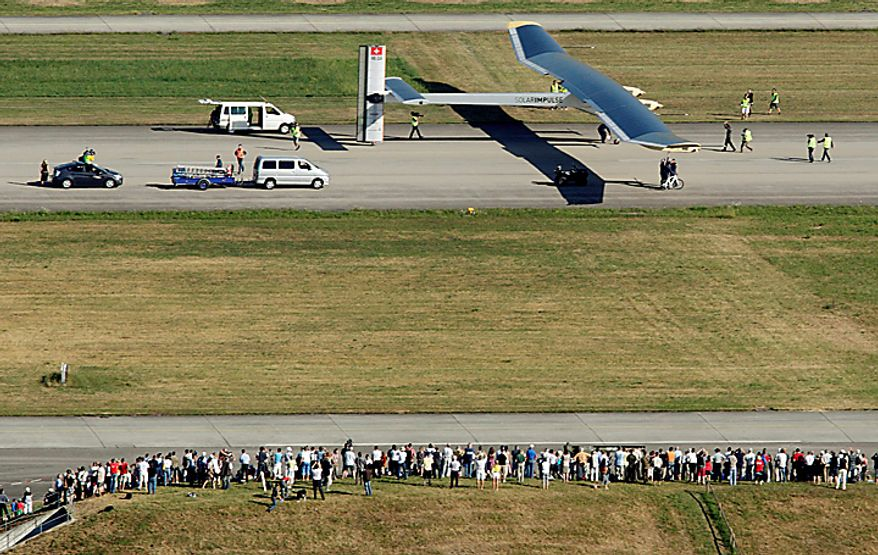 People look on as Solar Impulse's solar-powered HB-SIA prototype airplane stands on the runway after its first successful night flight attempt at Payerne airport, Thursday, July 8, 2010. The aircraft took off July 7 at 06:51 a.m. and reached an altitude of  28,543 feet by the end of the day. It then slowly descent to 4,921 feet and flew during the night on the batteries, charged during the day by 12,000 solar cells, which powered the four electric motors. It landed July 8 at 09.00 a.m. for a flight time of 26 hours and 9 minutes, setting the longest and highest flight ever made by a  solar plane. (AP Photo/Keystone, Denis Balibouse, Pool)