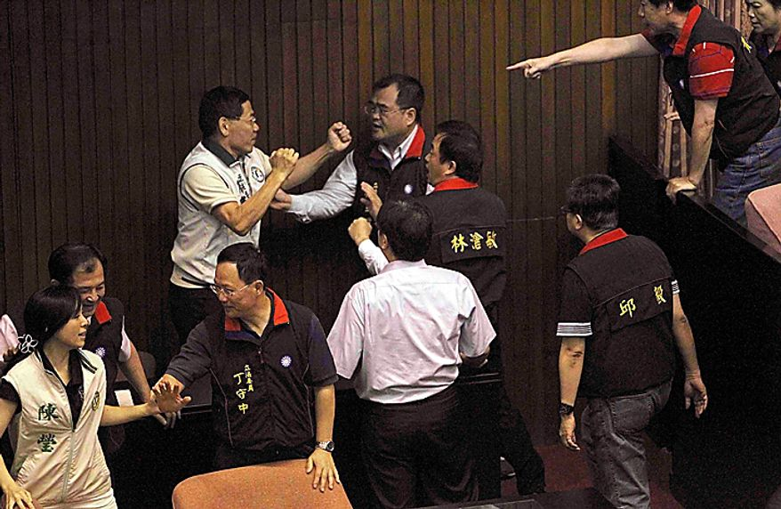 Ruling and opposition lawmakers brawl as discussions start on the Economic Cooperation Framework Agreement (ECFA) planned with China on the legislature floor on Thursday, July 8, 2010, in Taipei, Taiwan.  Lawmakers were seen shoving and punching each other in Taiwan's legislature after the speaker rejected an opposition bid to conduct a detailed debate on a contentious trade pact with China. (AP Photo/Wally Santana)