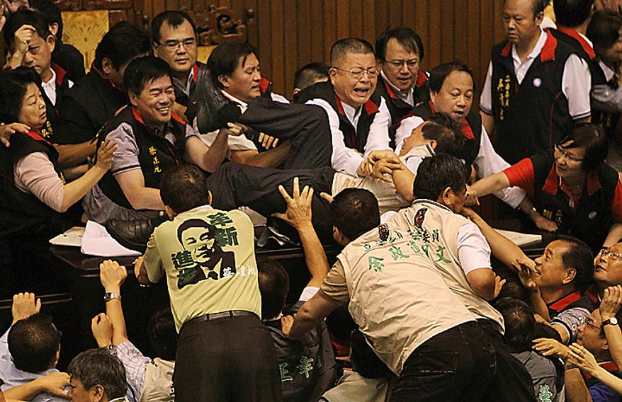Ruling, red collar  and opposition lawmakers brawl as discussions start on the Economic Cooperation Framework Agreement (ECFA) planned with China on the legislature floor on Thursday, July 8, 2010, in Taipei, Taiwan. Pro-and anti-government lawmakers exchanged punches and threw garbage bins at each other Thursday in another raucous session in Taiwan's legislature after the speaker rejected an opposition bid to conduct a detailed debate on a contentious trade pact with China. (AP Photo/Wally Santana)