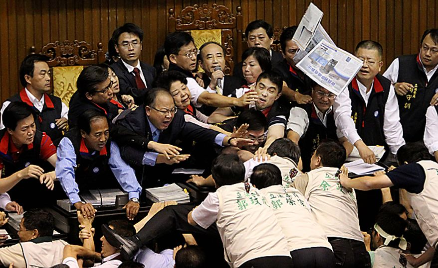 Speaker of the legislature, Wang Jin-pyng, top row center, tries to maintain order as legislators brawl on the legislature floor at the start of discussions on the Economic Cooperation Framework Agreement (ECFA) planned with China on Thursday, July 8, 2010, in Taipei, Taiwan. Lawmakers were seen shoving and punching each other in Taiwan's legislature after the speaker rejected an opposition bid to conduct a detailed debate on a contentious trade pact with China. (AP Photo/Wally Santana)