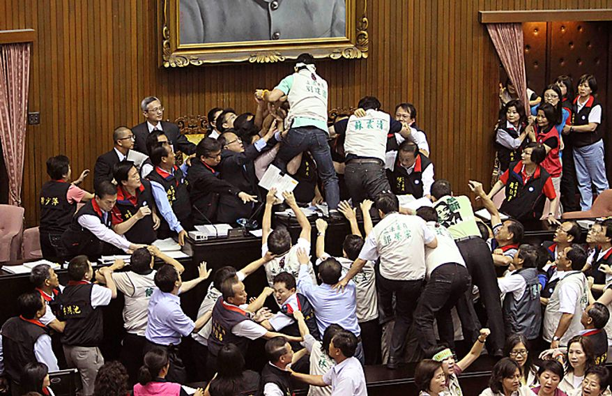 Ruling and opposition lawmakers brawl as discussions start on the Economic Cooperation Framework Agreement (ECFA) planned with China on the legislature floor, Thursday, July 8, 2010, in Taipei, Taiwan.  Lawmakers were seen shoving and punching each other in Taiwan's legislature after the speaker rejected an opposition bid to conduct a detailed debate on a contentious trade pact with China. (AP Photo/Wally Santana)