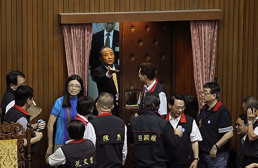 Taiwan's speaker of the legislature, Wang Jin-pyng, center, pleads with legislators to clear the floor as he enters to open a discussion session between parties on the Economic Cooperation Framework Agreement (ECFA) planned with China, Thursday, July 8, 2010, in Taipei, Taiwan. Opposition legislators chanted slogans as they protested the planned trade agreement with rival China, saying it will undermine the island's self-rule and its economy. (AP Photo/Wally Santana)