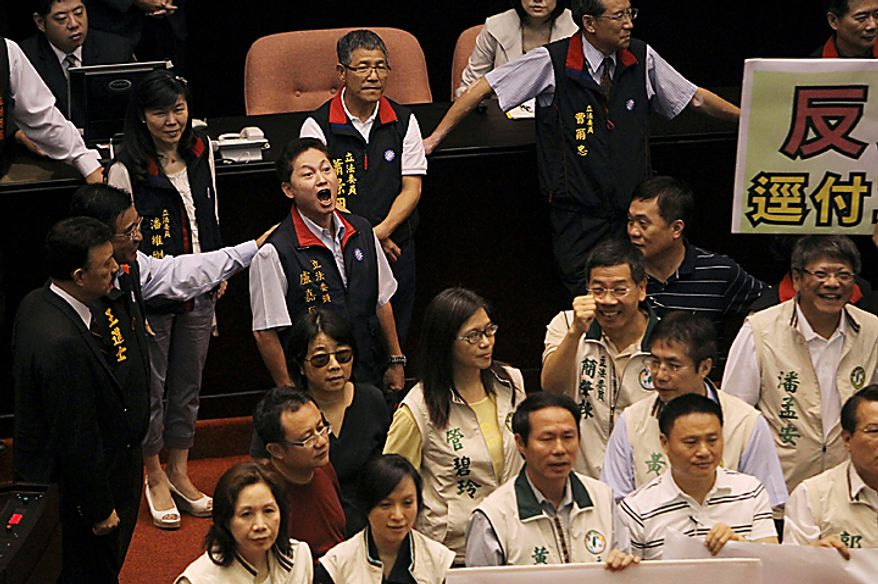 A ruling party legislator, in black vest, tries to drown out opposition attempts to denounce the Economic Cooperation Framework Agreement (ECFA) planned with China on the legislature floor as legislatures start a review of the ECFA, Thursday, July 8, 2010, in Taipei, Taiwan. Opposition legislators chanted anti-trade pact slogans as they protest the planned trade agreement with rival China saying it will undermine the island's self-rule and its economy. (AP Photo/Wally Santana)