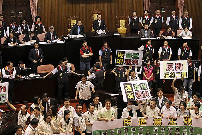 "Opposition lawmakers, front, chant slogans and hold placards denouncing the Economic Cooperation Framework Agreement (ECFA) planned with China on the legislature floor as legislatures start a review of the ECFA, Thursday, July 8, 2010, in Taipei, Taiwan. Opposition legislators chanted anti-trade pact slogans as they protested the planned trade agreement with rival China saying it will undermine the island's self-rule and its economy. The placards read, ""Review the trade deal piece by piece, not as a whole package."" (AP Photo/Wally Santana)"