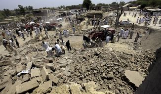 People gather near the site of the suicide bombing in Yakaghund in Pakistani tribal area of Mohmand on Friday, July 9, 2010. A suicide bomber on a motorcycle struck outside a government office Friday in a tribal region where Pakistan's army has fought the Taliban, killing scores of people and left many injured, officials said.(AP Photo/Mohammad Sajjad)