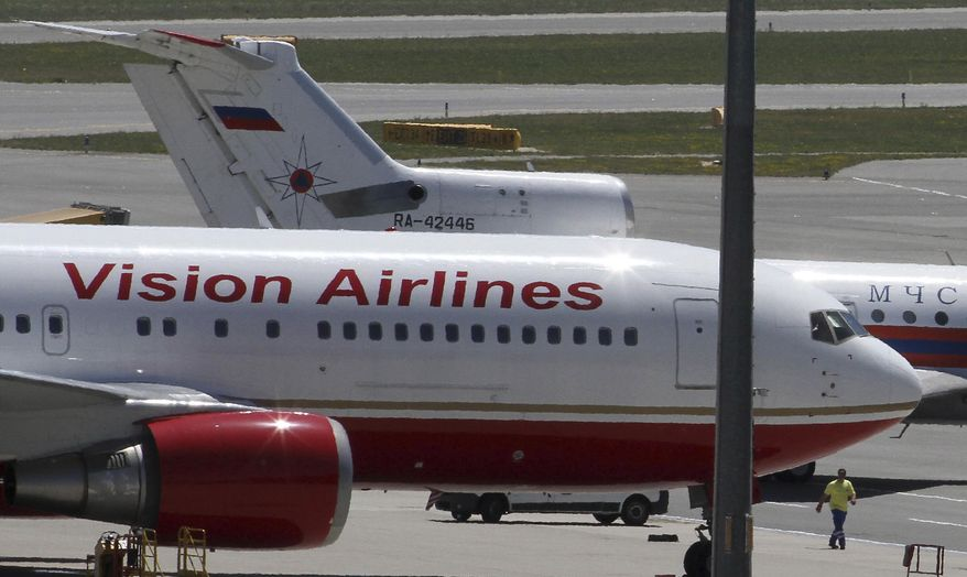A U.S. plane, front, and a Russian plane, rear, believed to be carrying candidates for a 14-person spy swap as part of the largest spy swap since the Cold War stand on the tarmac at Vienna's Schwechat airport, Austria, on Friday, July 9, 2010. (AP Photo/Ronald Zak)