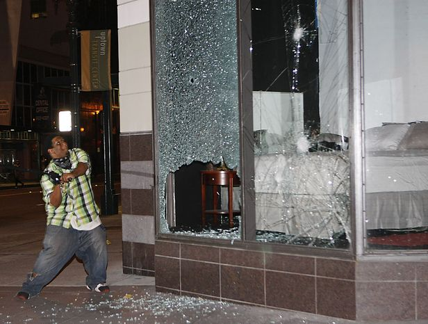 A protester breaks a window at Sears store during a demonstration in Oakland, Calif., after a guilty verdict for Johannes Mehserle, Thursday, July 8, 2010.  Former San Francisco Bay Area Rapid Transit police officer Johannes Mehserle was found guilty in Los Angeles for shooting unarmed black man Oscar Grant on New Year's Day 2009 at a BART station in Oakland.  (AP Photo/Paul Sakuma)