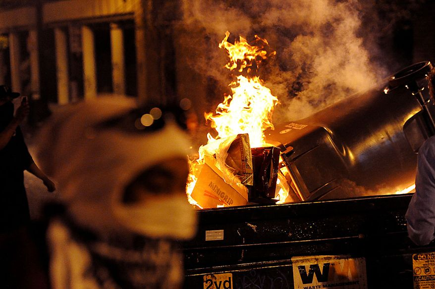 A dumpster burns during protesting in Oakland, Calif., following an involuntary manslaughter verdict in Johannes Mehserle's trial on Thursday, July 8, 2010. A former transit police officer, Mehserle shot and killed unarmed black man Oscar Grant on New Year's Day 2009. (AP Photo/Noah Berger)