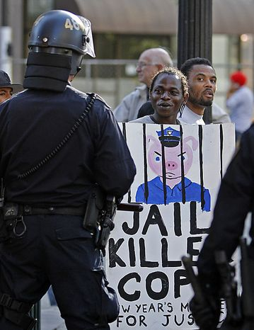 A protester taunts policemen during a protest of the verdict of involuntary manslaughter given to Johannes Mehserle Thursday, July 8, 2010, in Oakland, Calif. Former Bay Area Rapid Transit police officer Johannes Mehserle was found guilty in Los An
