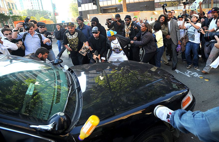 Protesters chase back a police car in Oakland, Calif., following an involuntary manslaughter verdict in Johannes Mehserle's trial on Thursday, July 8, 2010. A former transit police officer, Mehserle shot and killed unarmed black man Oscar Grant on New Year's Day 2009.  (AP Photo/Noah Berger)