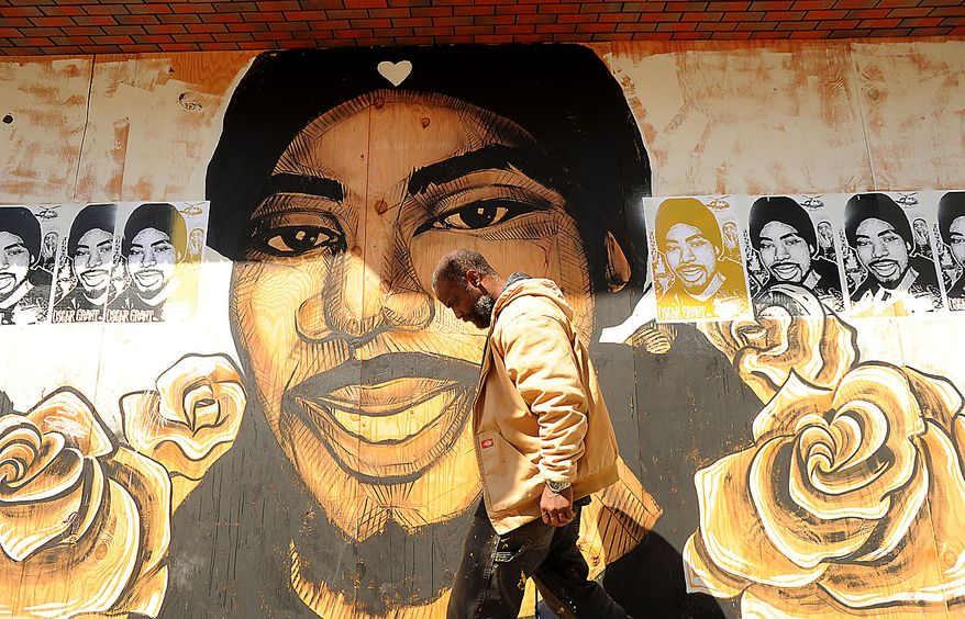 A pedestrian passes a mural of Oscar Grant in Oakland, Calif., shortly before a jury delivered an involuntary manslaughter verdict in Johannes Mehserle's trial on Thursday, July 8, 2010. (AP Photo/Noah Berger)