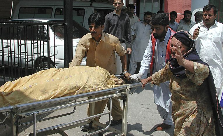 People carry an injured person to a local hospital in Peshawar, Pakistan on Friday, July 9, 2010. Two suicide bombers, at least one of them on a motorcycle, struck outside a government office Friday in a tribal region where Pakistan's army has fought the Taliban, killing scores of people and left many injured, officials said. (AP Photo/Mohammad Iqbal)