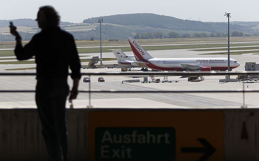 A U.S., front, and a Russian plane, rear, believed to be carrying candidates for a 14-person spy swap as part of the largest spy swap since the Cold War have parked on the tarmac at Vienna's Schwechat airport on Friday, July 9, 2010. (AP Photo/Matthias Schrader)