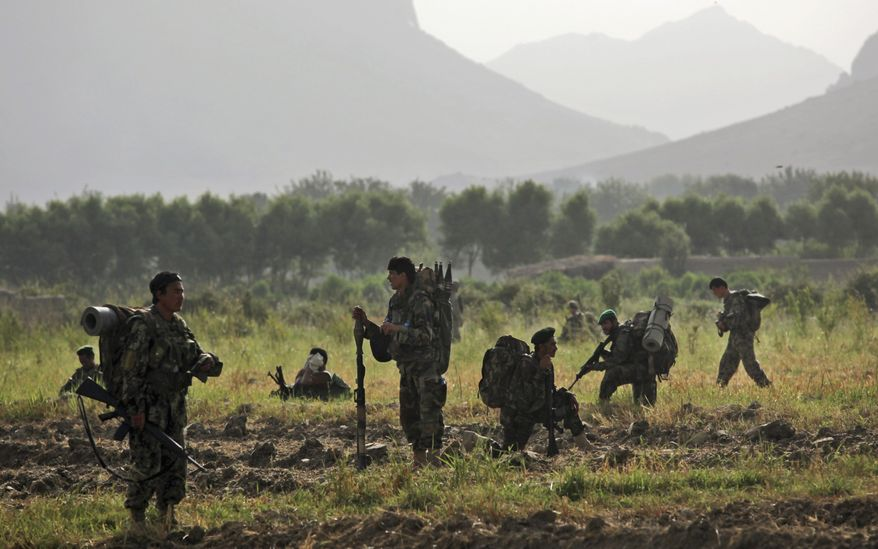 In this photo taken Thursday, July 8, 2010, Afghan soldiers pause during a patrol with United States Army soldiers from Bravo Company, 2nd Battalion of the 508 Parachute Infantry Regiment of the 82nd Airborne, in the volatile Arghandab Valley, outside Kandahar City. (AP Photo/Kevin Frayer)