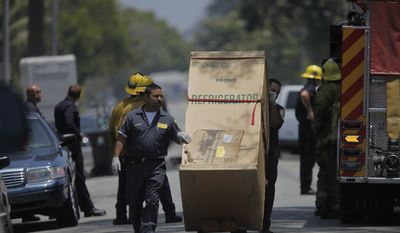 Los Angeles Police assistants take away a refrigerator, as investigators gather evidence at the home of suspect Lonnie David Franklin Jr. on Friday, July 9, 2010, in Los Angeles. (AP Photo/Damian Dovarganes)
