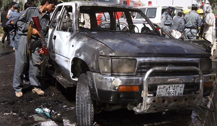 An Afghan policeman inspects a damaged vehicle at the scene of an explosion in Kandahar south of Kabul, Afghanistan on Saturday, July 10, 2010. One bystander was killed when the bomb, concealed in a parked motorcycle, exploded in the middle of the afternoon, said the city's security chief. (AP Photo/Allauddin Khan)