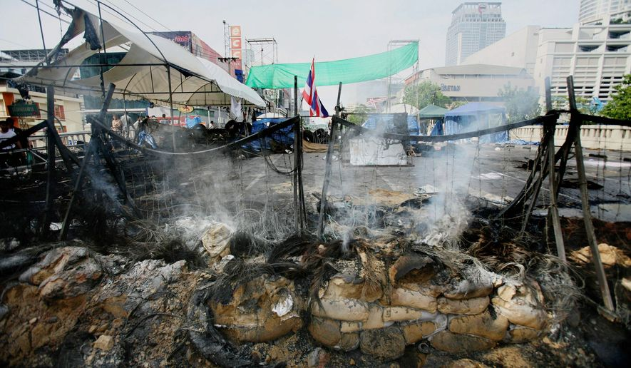 "Roadblocks surrounding the former ""Red Shirt"" protest zone smolder after a massive arson attack on the major shopping district in May in Bangkok. Buildings smoldered across central Bangkok and troops exchanged sporadic fire with pockets of holdouts a day after the army routed anti-government protesters in a push to end Thailand's deadliest political violence in nearly 20 years. (Associated Press)"