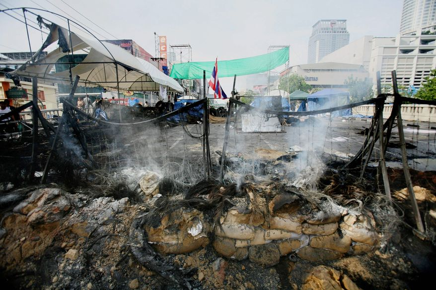 """Roadblocks surrounding the former """"Red Shirt"""" protest zone smolder after a massive arson attack on the major shopping district in May in Bangkok. Buildings smoldered across central Bangkok and troops exchanged sporadic fire with pockets of holdouts a day after the army routed anti-government protesters in a push to end Thailand's deadliest political violence in nearly 20 years. (Associated Press)"""