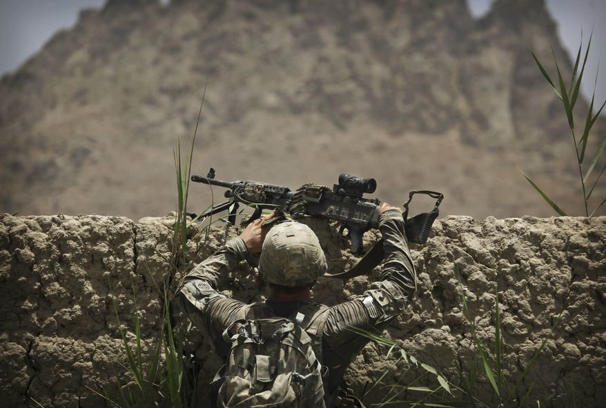 A U.S. Army soldier from Bravo Company, 2nd Battalion of the 508 Parachute Infantry Regiment of the 82nd Airborne, climbs over a high wall during a patrol in the volatile Arghandab Valley outside Kandahar City, Afghanistan, on Saturday, July 10, 2010. (AP Photo/Kevin Frayer)