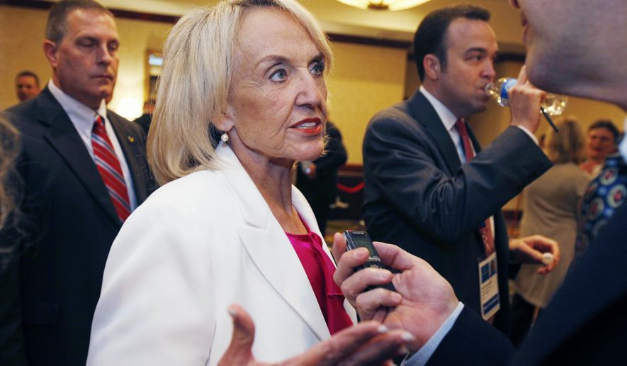 Arizona Gov. Jan Brewer speaks with a reporter about her meeting with U.S. Secretary of Homeland Security Janet Napolitano at the annual meeting of the National Governors Association on Sunday, July 11, 2010, in Boston. (AP Photo/Michael Dwyer)