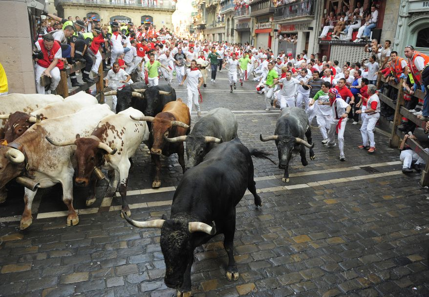 Fighting bulls from Spain's famed Miura ranch head down the course during the fifth day of the running of the bulls at the San Fermin festival in Pamplona, Spain, on Sunday, July 11, 2010. (AP Photo/Manu Fernandez)