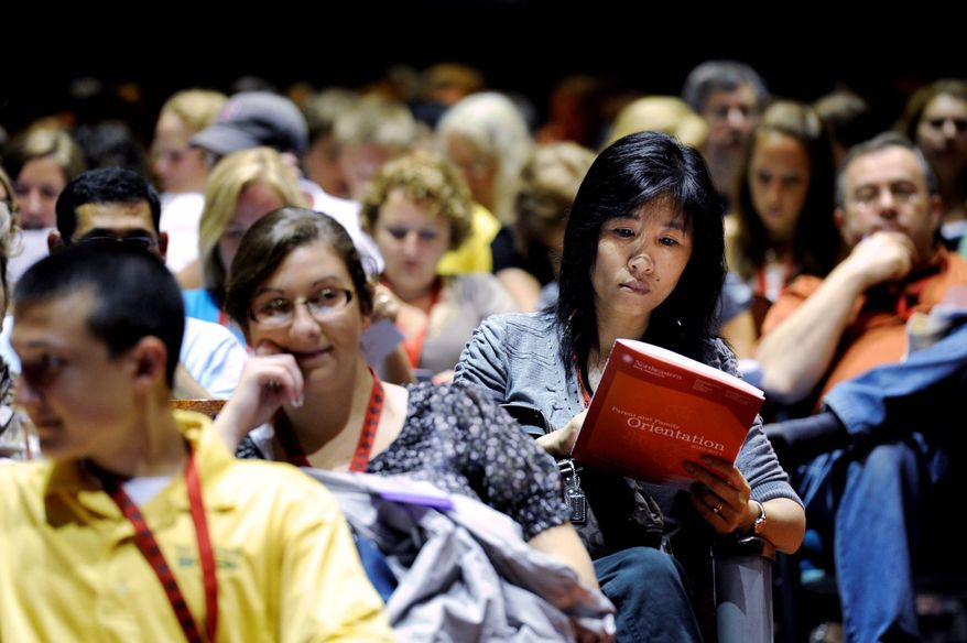 Parent Landi Tang looks over a booklet during an orientation for families of incoming freshmen at Northeastern University in Boston. Some orientations for families are packed with workshops, tours and speeches on subjects ranging from letting go to campus safety. Some such events last two or even three days and require hefty sign-up fees in addition to the cost of travel. (Associated Press)