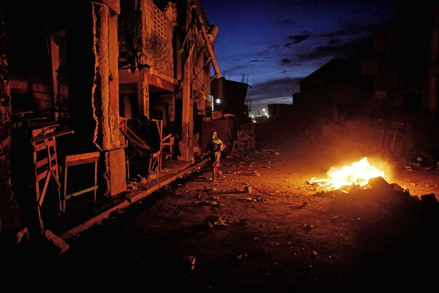 Garbage burns through the night in Port-au-Prince, Haiti, where about 80 percent of the buildings were destroyed. Government officials cannot say where they will get the $100 million pledged for reconstruction. (Associated Press)