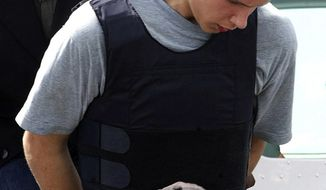 A handcuffed Colton Harris-Moore exits a plane under police escort upon arrival in Nassau, Bahamas, on Sunday, July 11, 2010. (AP Photo/Felipe Major)