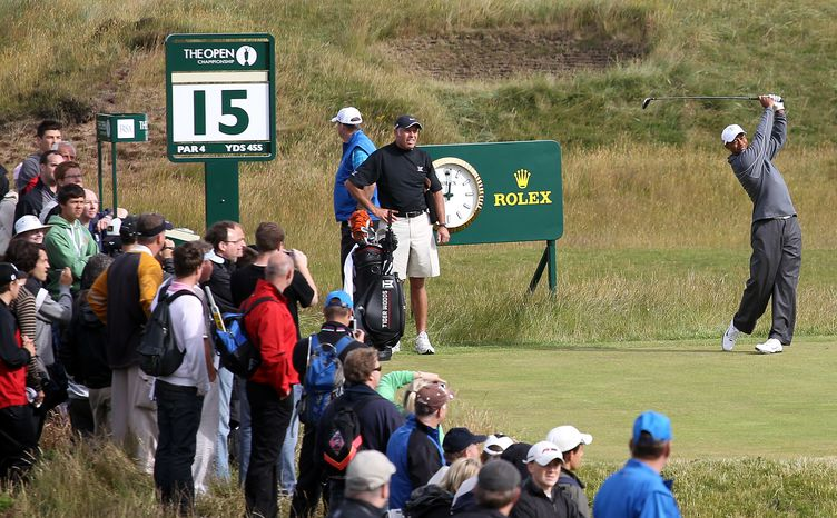U.S. Tiger Woods, right, tees off on the 15th hole at the Old Course at St. Andrews, Scotland, on Monday, July, 12, 2010. Players continue their preparations for The Open golf championship which starts on Thursday. (AP Photo/Peter Morrison)