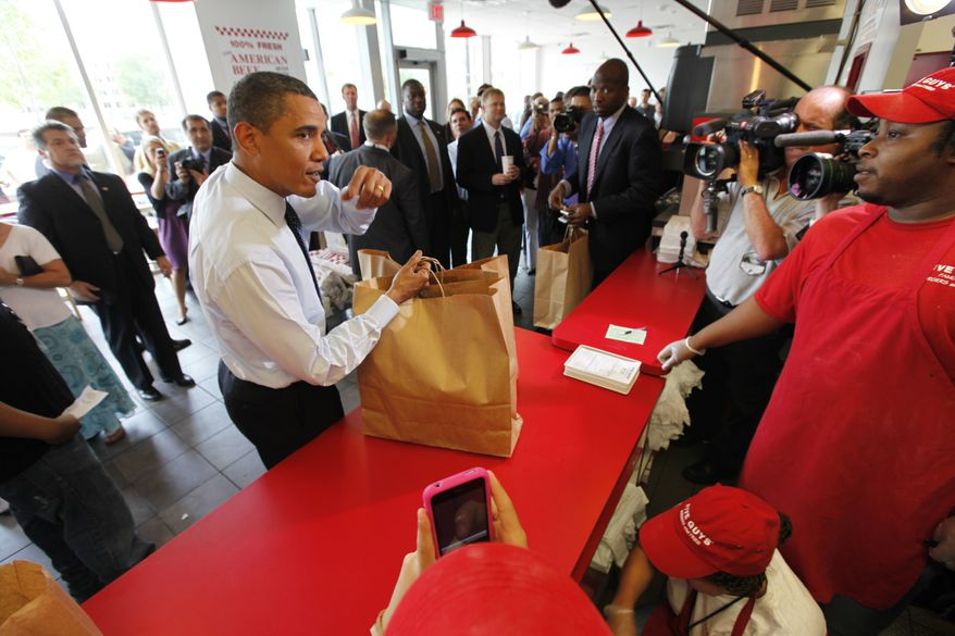 ** FILE ** In this May 29, 2009 file photo, President Barack Obama orders a hamburger at the Five Guys Burgers and Fries in Washington. With a drive-through seemingly on every corner, you might think the burger market long ago reached saturation. But the fastest-growing restaurant chain in America last year was Five Guys, which specializes in double-pattied behemoths. (AP Photo/Gerald Herbert, file)