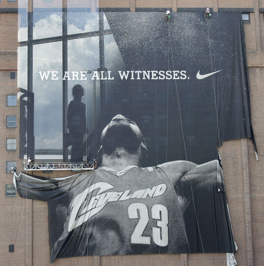 ASSOCIATED PRESS A child is seen reflected in the fifth-floor window of a parking garage across the street from where workers remove the giant banner of former Cleveland Cavaliers basketball star LeBron James in downtown Cleveland on Sunday, July 11, 2010. On Thursday night, James announced that he will play for the Miami Heat next season.