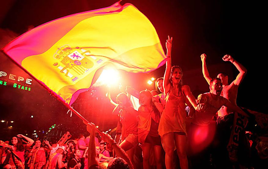 Under the light of flares, Spanish fans celebrate in a fountain in downtown Madrid after Spain defeated the Netherlands to win the World Cup soccer final in South Africa, on Sunday, July 11, 2010. Spain won 1-0. (AP Photo/Arturo Rodriguez)