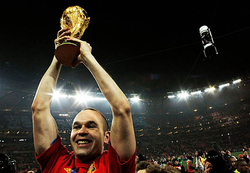 Spain's Andres Iniesta holds up the World Cup trophy following the World Cup final soccer match between the Netherlands and Spain at Soccer City in Johannesburg, South Africa, Sunday, July 11, 2010. (AP Photo/Bernat Armangue)