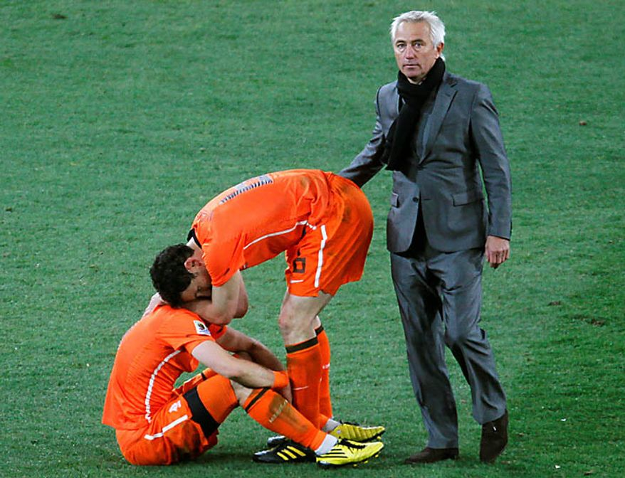 Netherlands head coach Bert van Marwijk, right, comfort his players after the World Cup final soccer match between the Netherlands and Spain at Soccer City in Johannesburg, South Africa, Sunday, July 11, 2010. Spain won 1-0. (AP Photo/Eugene Hoshiko)