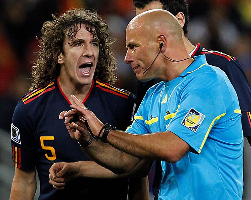 Spain's Carles Puyol, left, argues with English referee Howard Webb during the World Cup final soccer match between the Netherlands and Spain at Soccer City in Johannesburg, South Africa, Sunday, July 11, 2010. (AP Photo/Bernat Armangue)