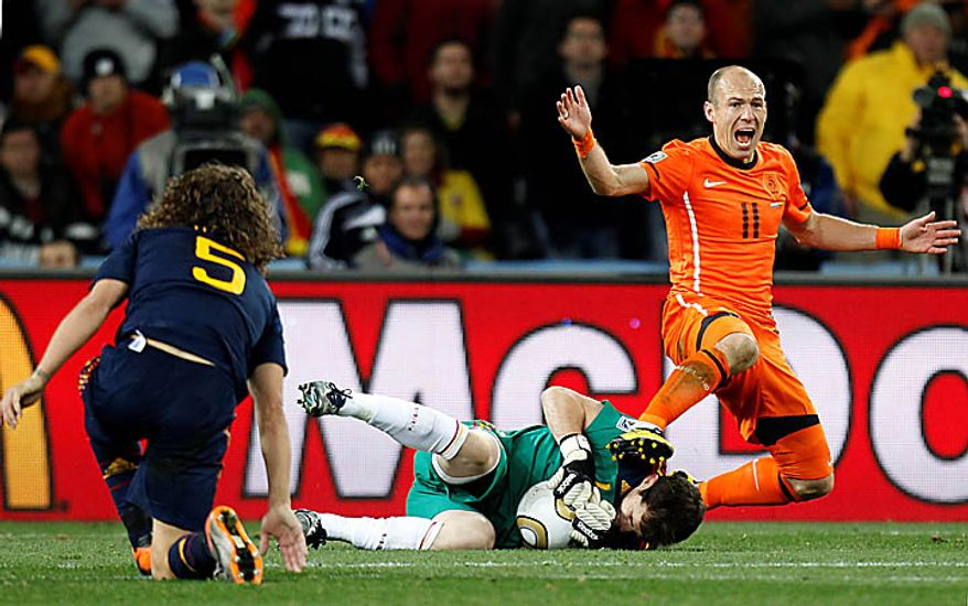 Netherlands' Arjen Robben, right, reacts as Spain goalkeeper Iker Casillas, center, grabs the ball next to Spain's Carles Puyol, left, during the World Cup final soccer match between the Netherlands and Spain at Soccer City in Johannesburg, South Africa, Sunday, July 11, 2010. (AP Photo/Luca Bruno)