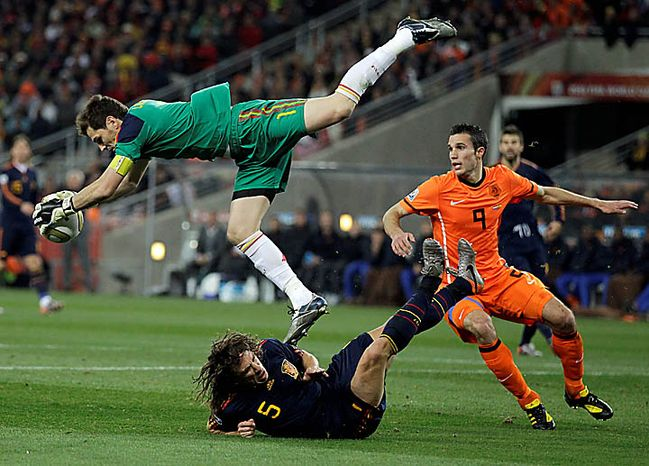 Spain goalkeeper Iker Casillas, left, makes a save above Netherlands' Robin van Persie, right, and Spain's Carles Puyol, bottom, during the World Cup final soccer match between the Netherlands and Spain at Soccer City in Johannesburg, South Africa, Sunday, July 11, 2010. (AP Photo/Matt Dunham)