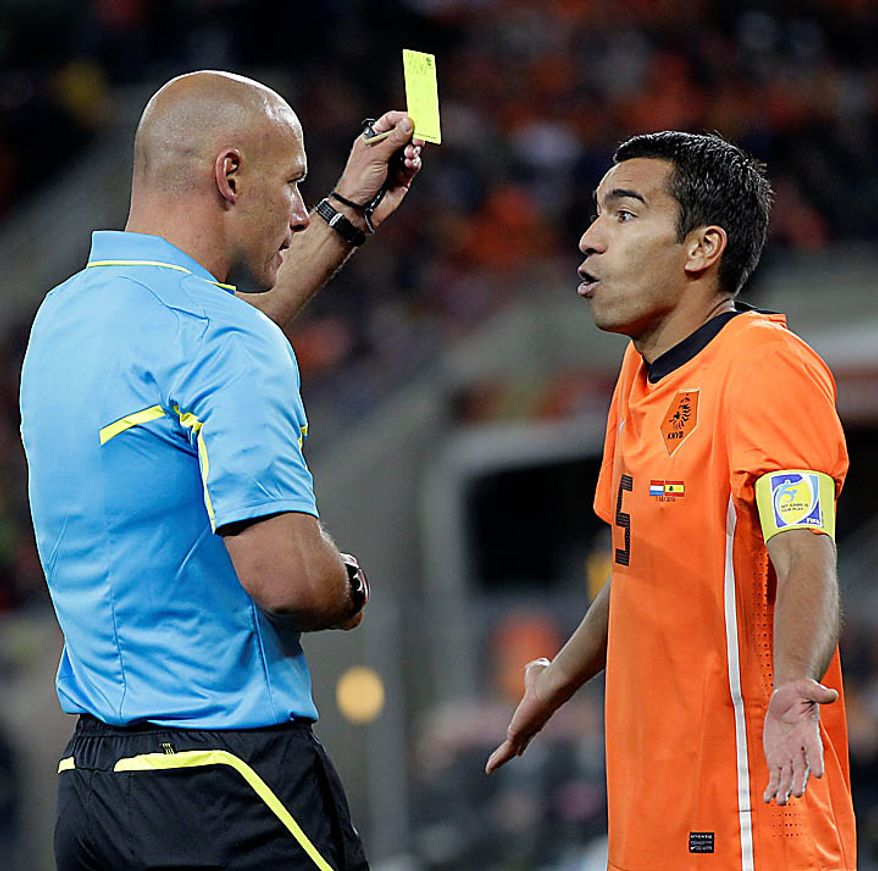 Referee Howard Webb, left, gives a yellow card to Netherlands' Giovanni van Bronckhorst during the World Cup final soccer match between the Netherlands and Spain at Soccer City in Johannesburg, South Africa, Sunday, July 11, 2010. (AP Photo/Frank Augstein)