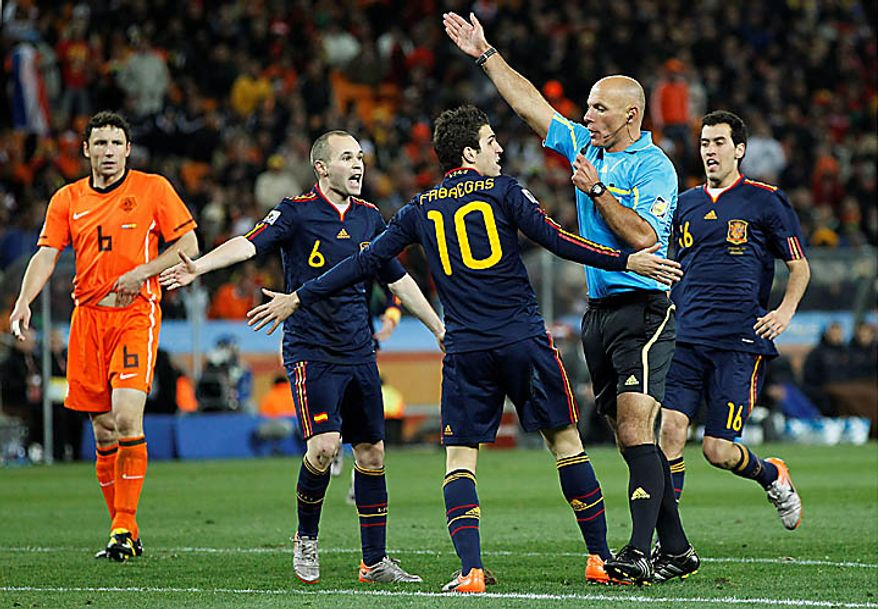 Spain's Cesc Fabregas, center with back to camera, and Spain's Andres Iniesta, second from left, contest a decision by referee Howard Webb, of England, second from right, during the World Cup final soccer match between the Netherlands and Spain at Soccer City in Johannesburg, South Africa, Sunday, July 11, 2010. (AP Photo/Bernat Armangue)